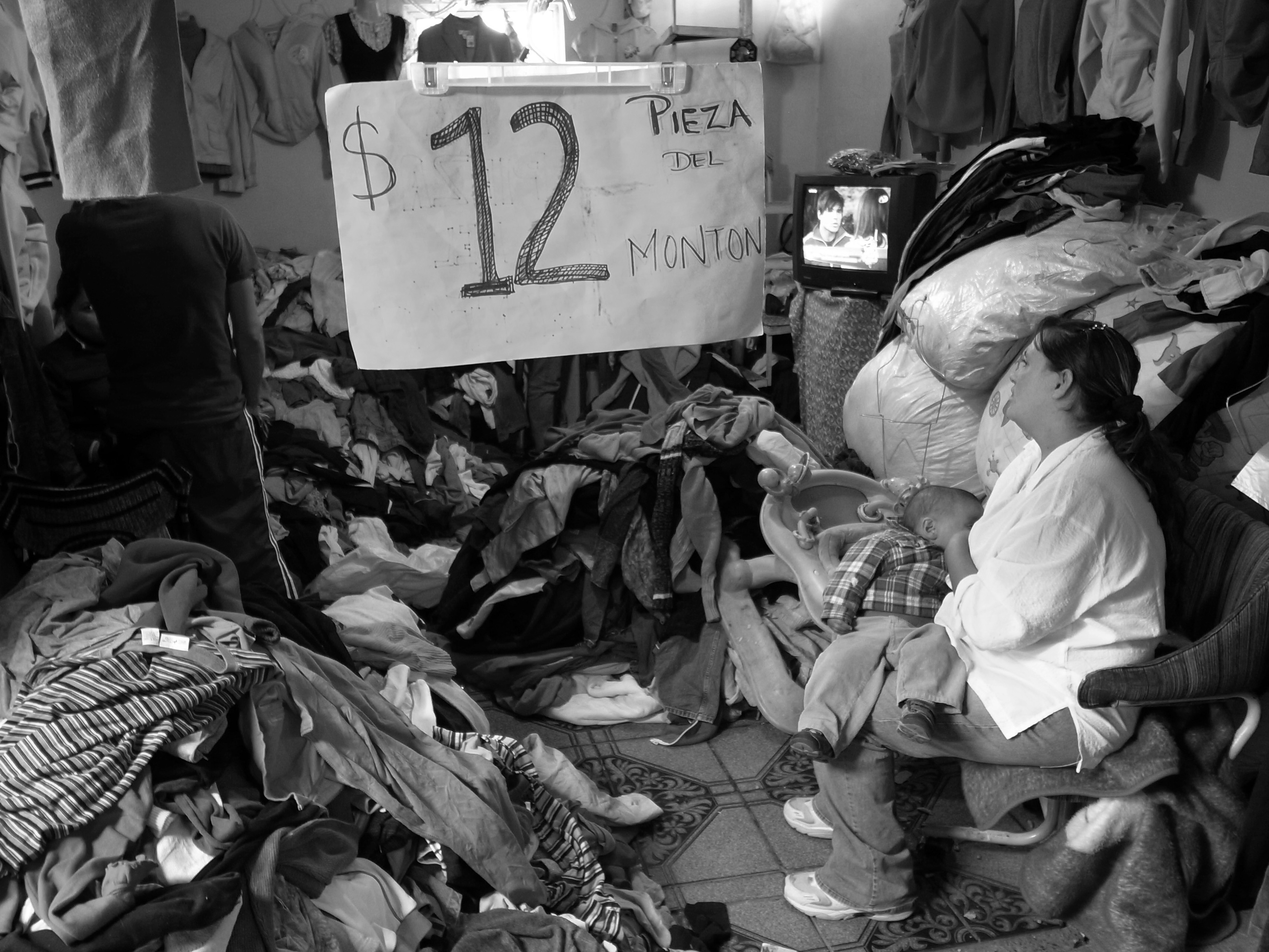 A woman nursing a baby sits amidst piles of clothes and a sign showing a price