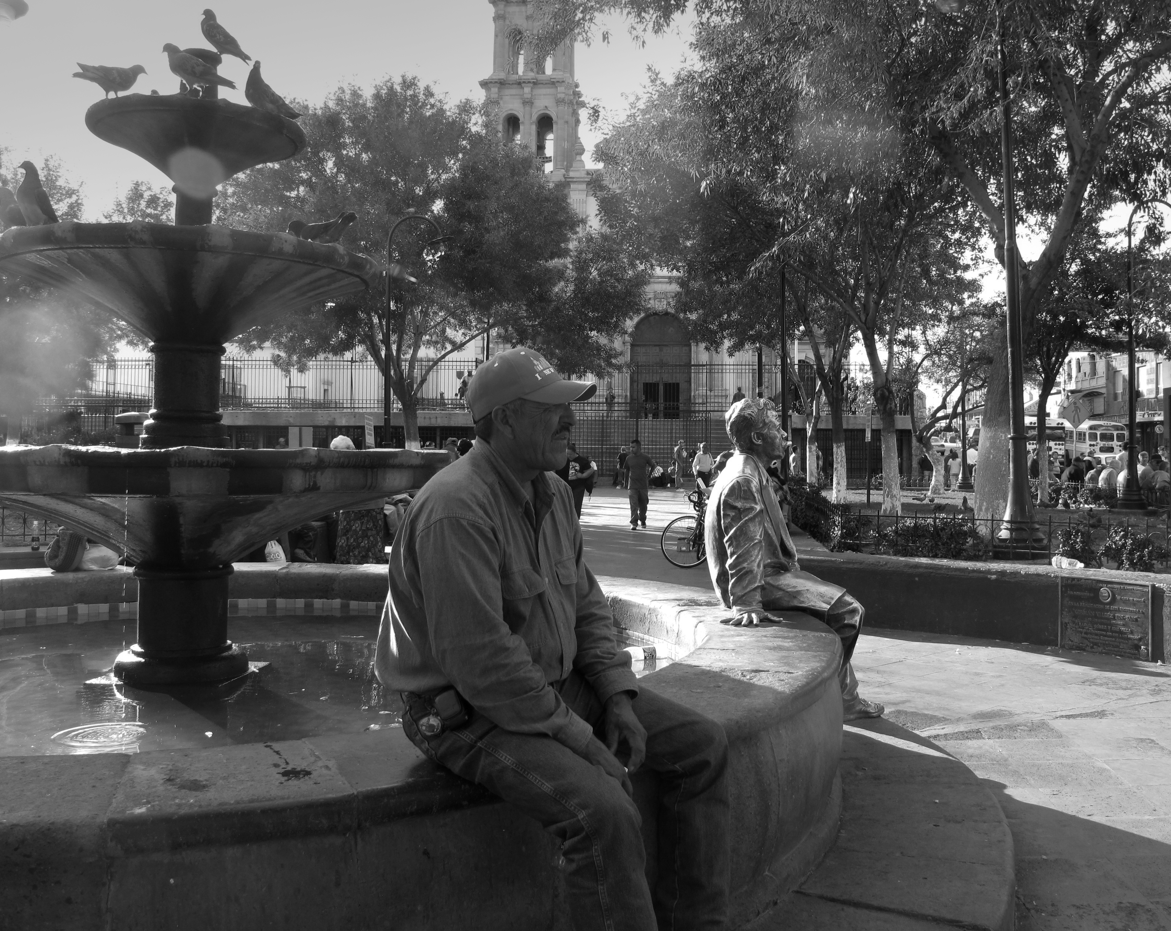 A man sits at a fountain next to a life size sculpture of a man in a park