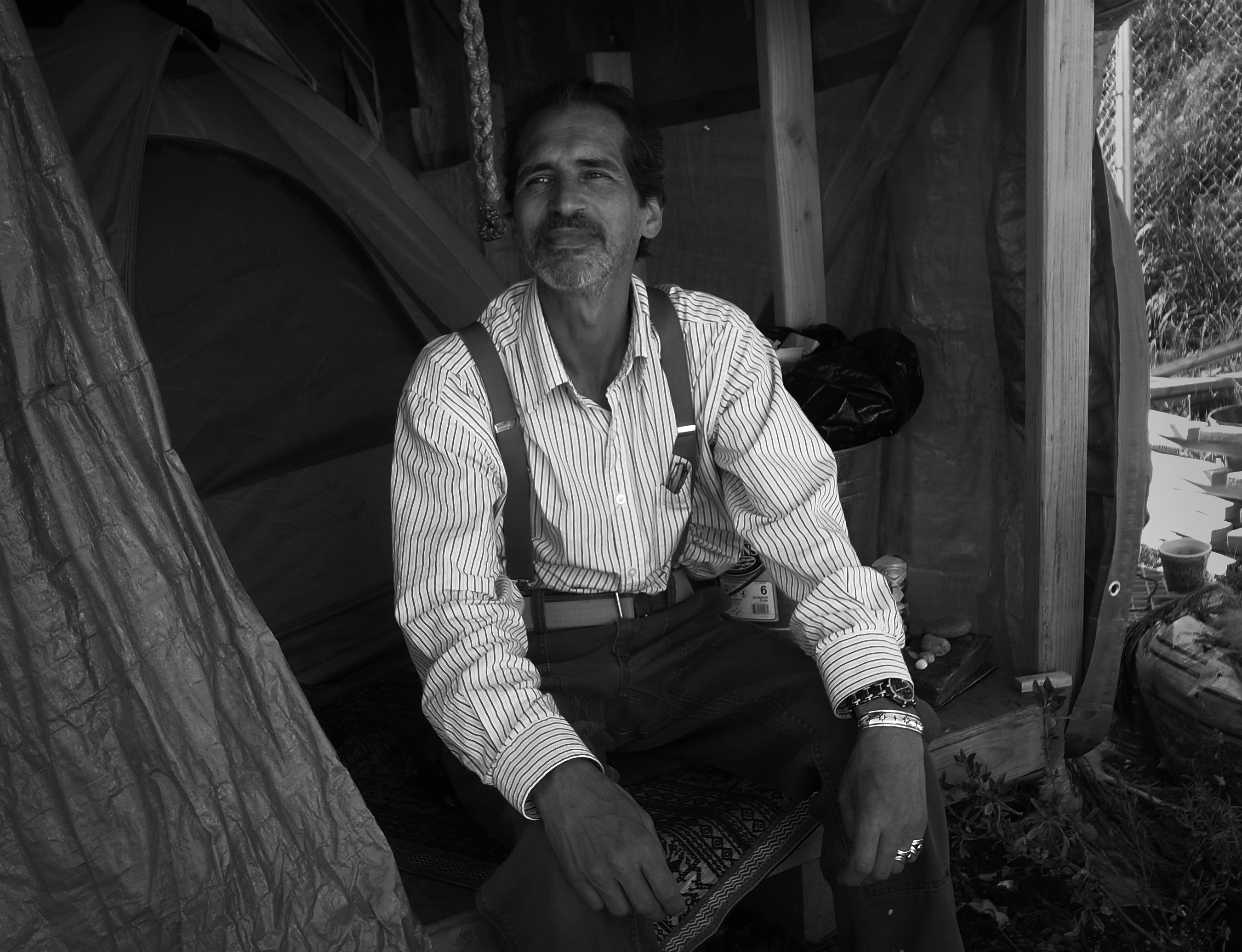 A man in suspenders sits at a tent entrance