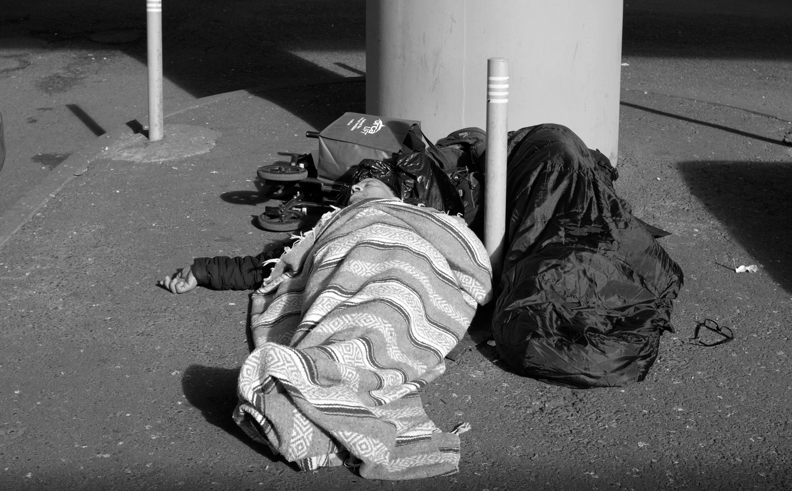 A man sleeping under a blanket on the street