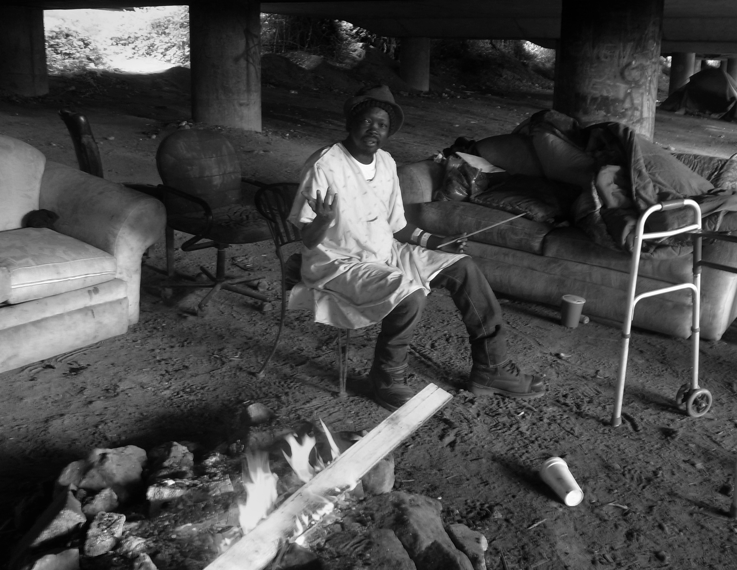 A man wearing a hospital gown and a hat infront of a fire under an overpass