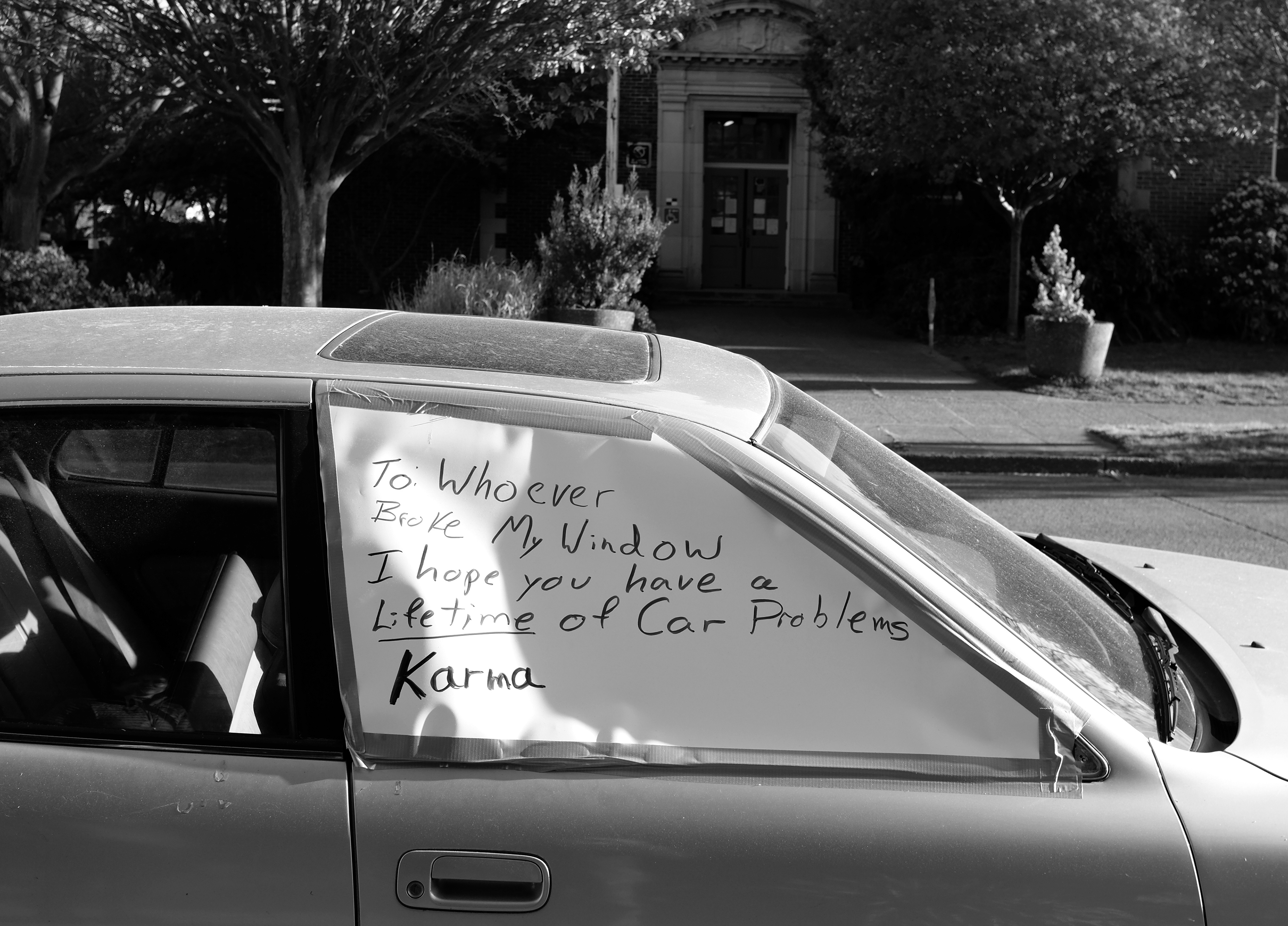 "A large note covers a broken car window. It reads ""To whoever broke my window I hope you have a lifetime of car problems karma"""