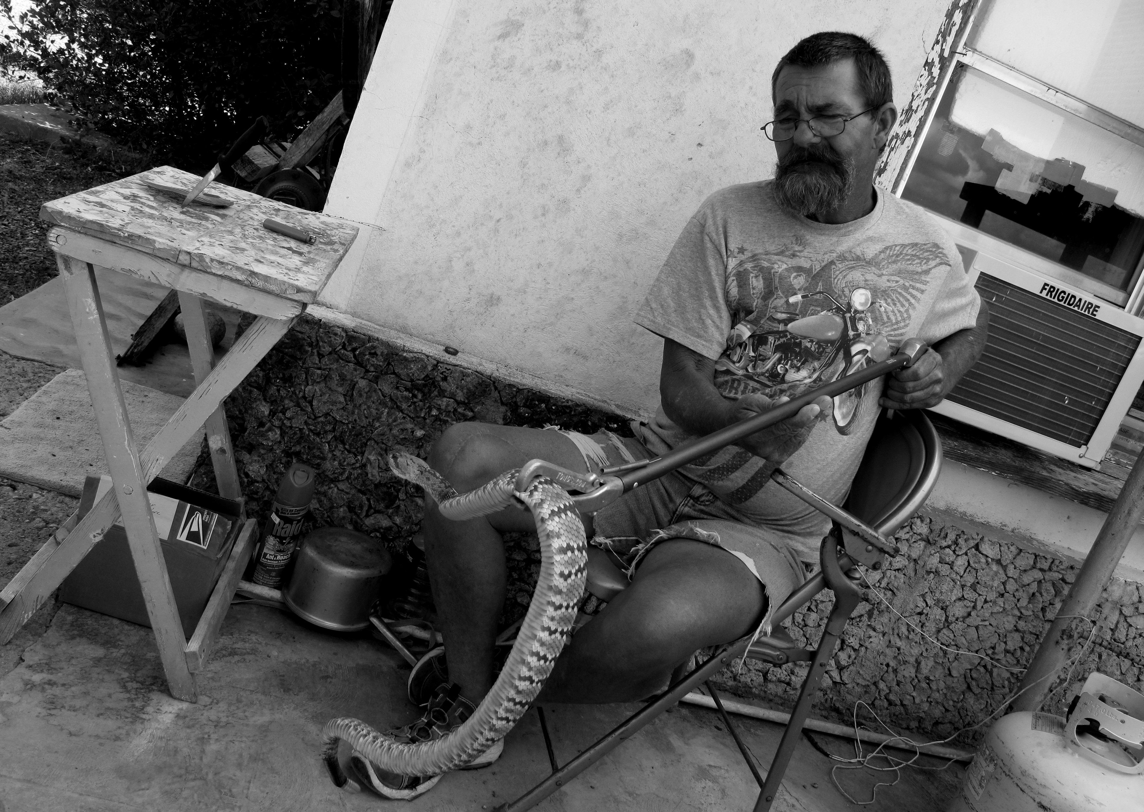 A man sitting on a chair holds a rattle snake in a gripper outside of a building