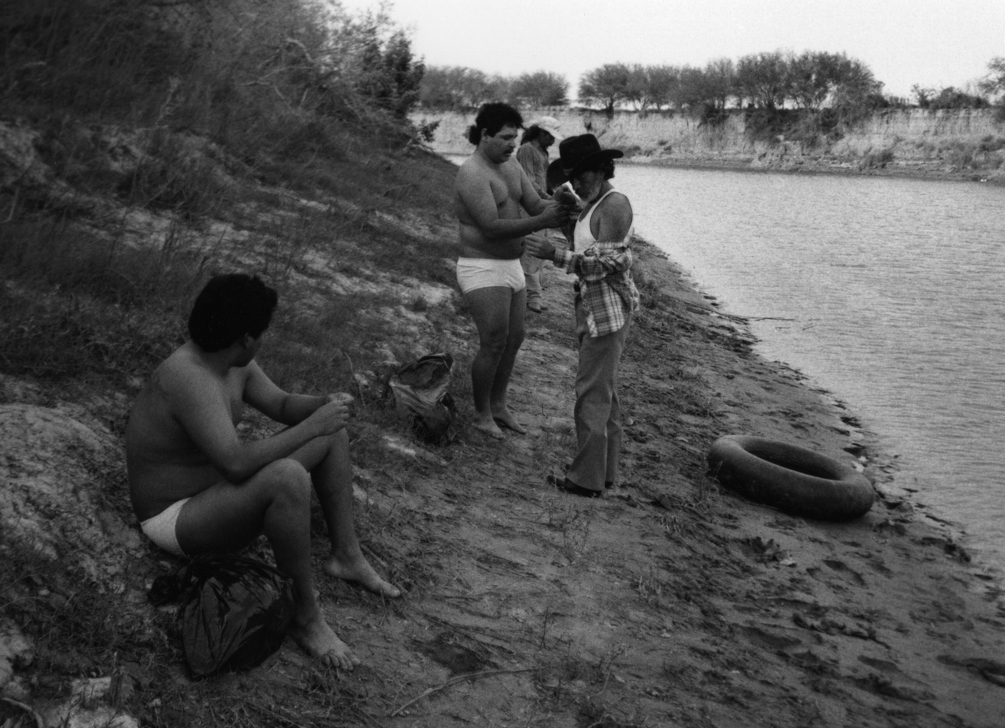 Men stripped or stripping to their underwear on a river bed