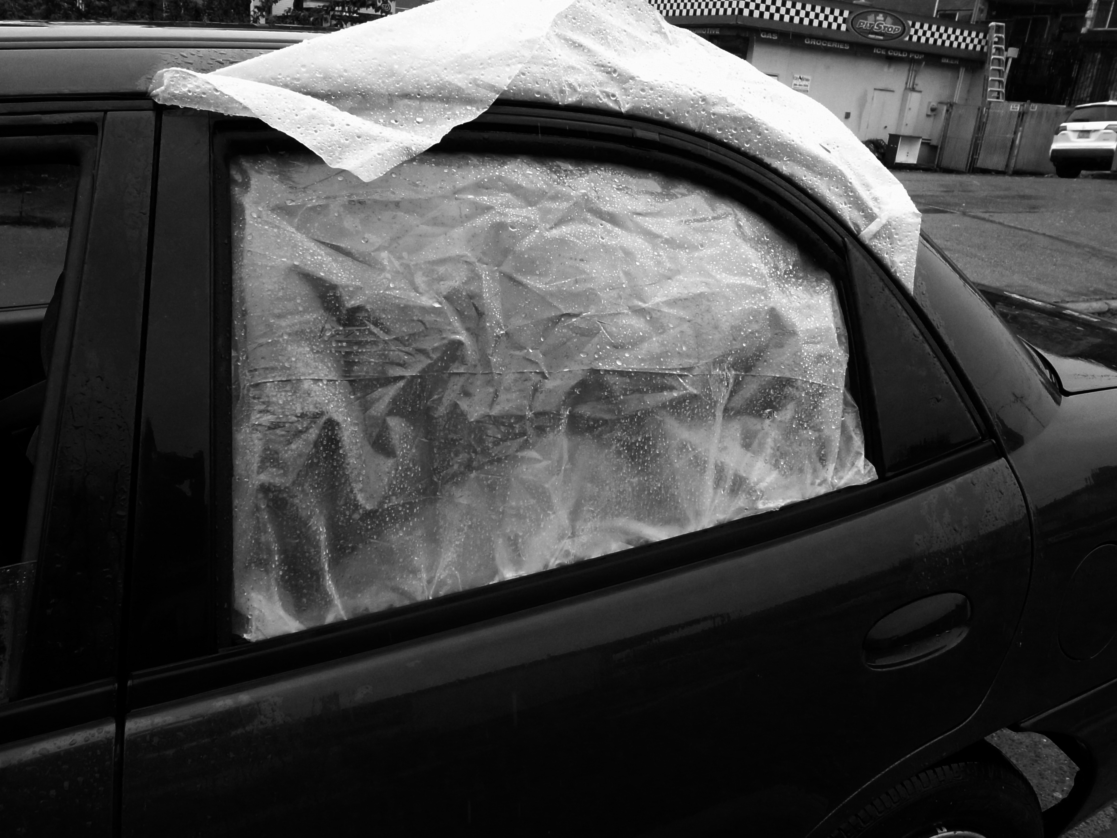A rain covered translucent plastic covers the boken window of a car