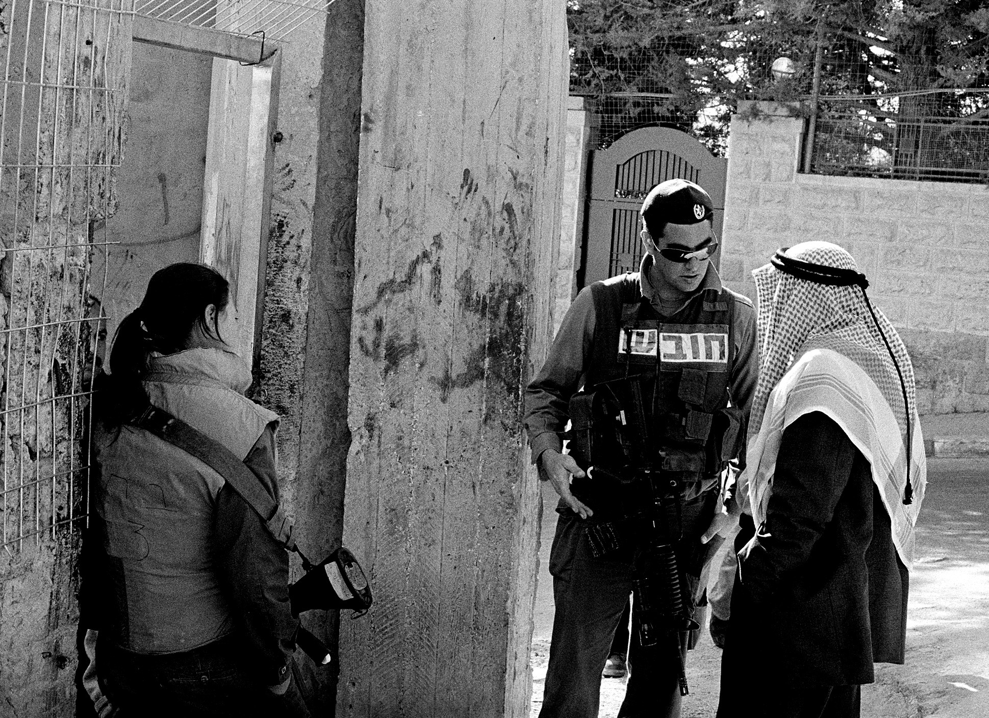 A young male soldier speaks with an arab man while a female soldier leans on a wall