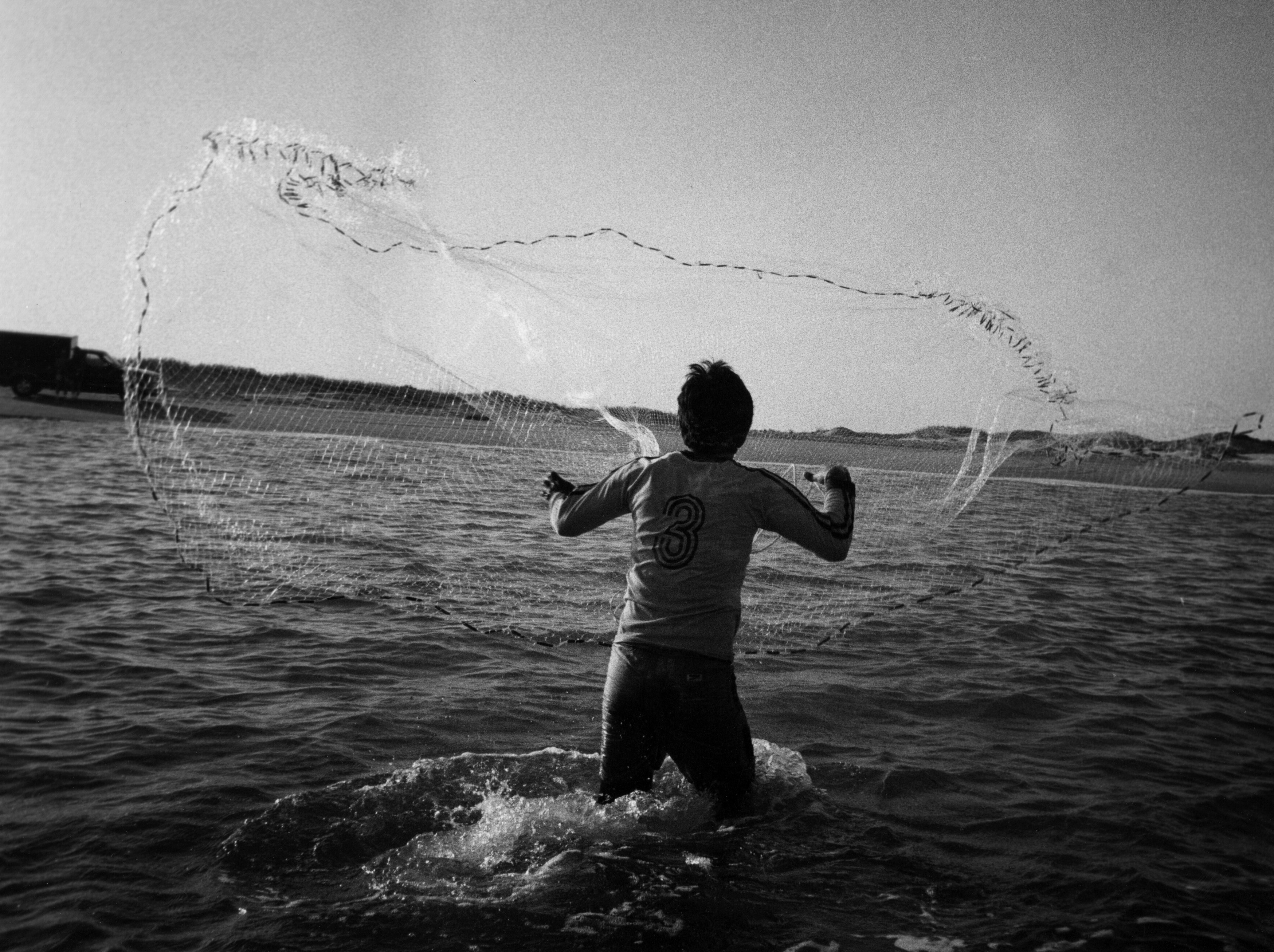 A young man in knee-deep sea casts a net