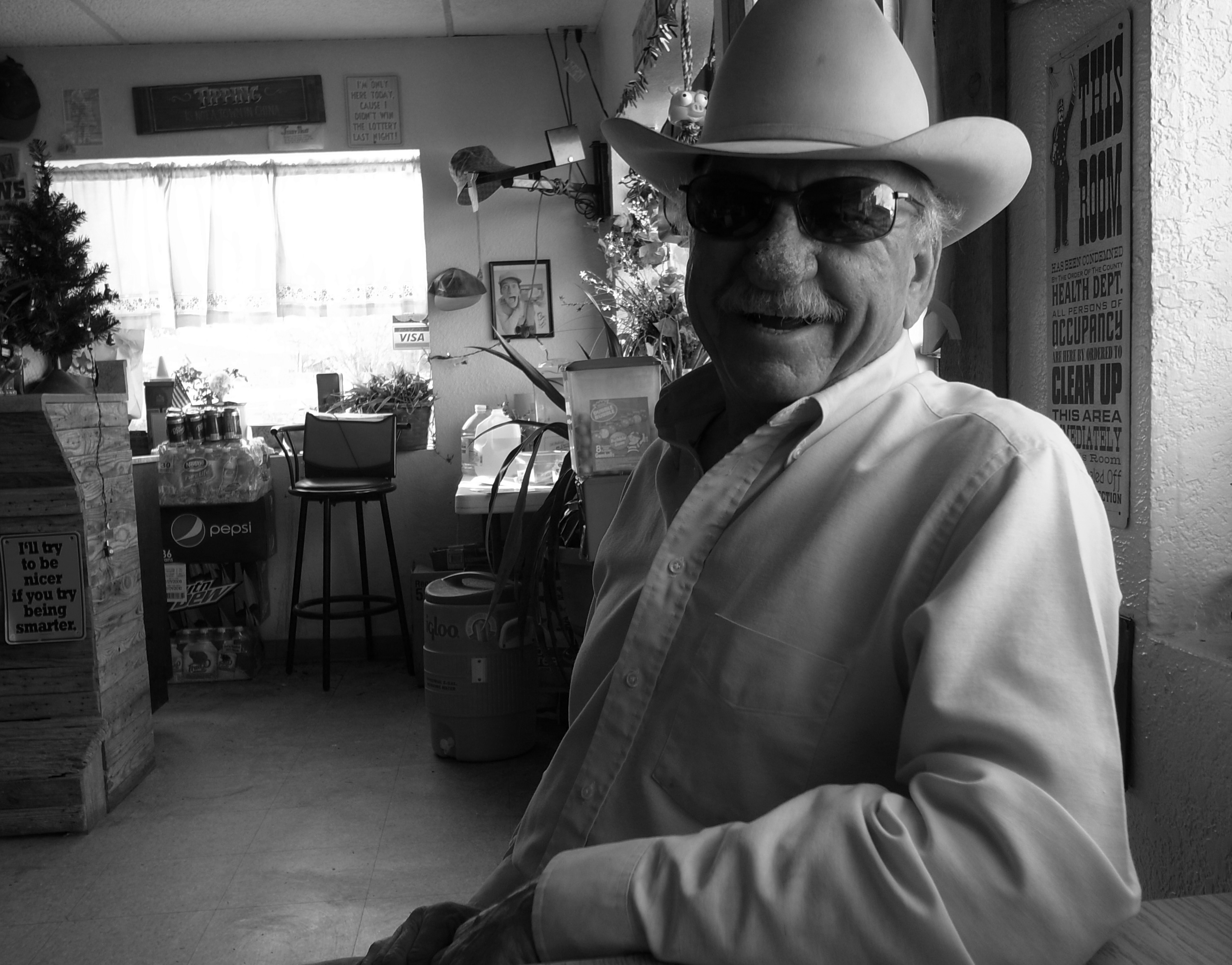 An older man in sunglasses and a cowboy hat smiles inside a cafe