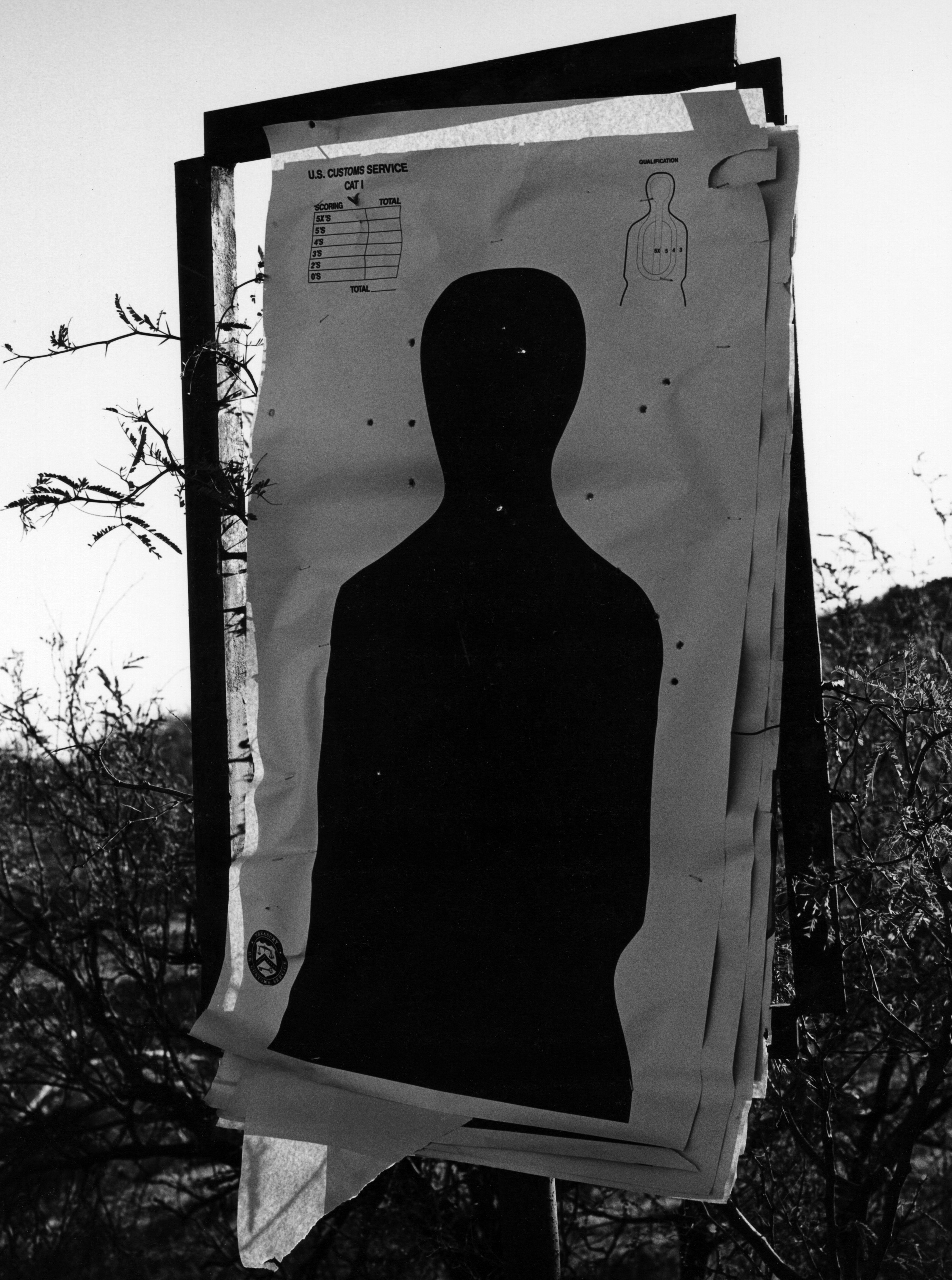 The silhouette of a person on a target with bullet holes