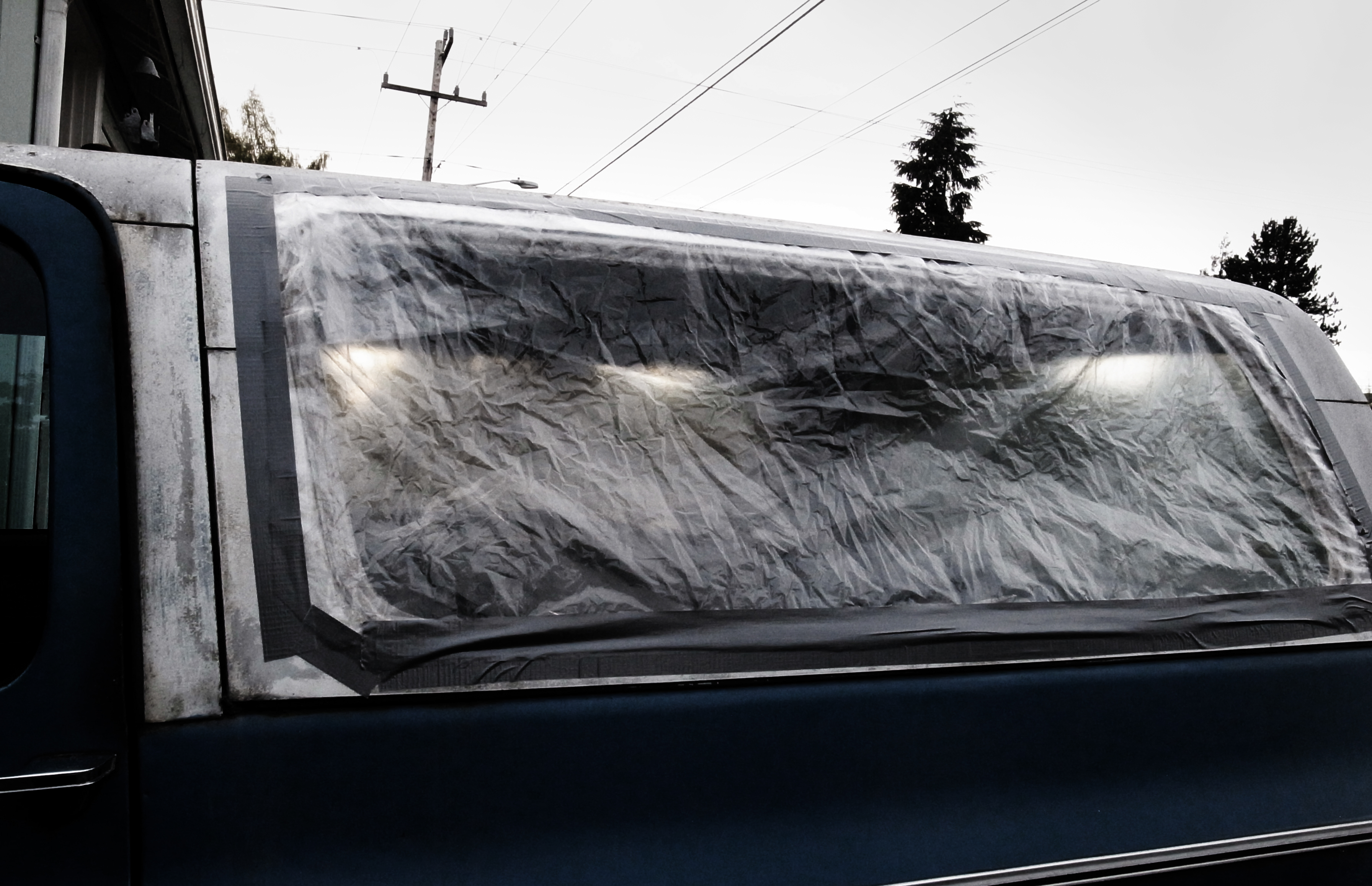 Translucent plastic and duct tape covers the broken window of a pick up truck shell