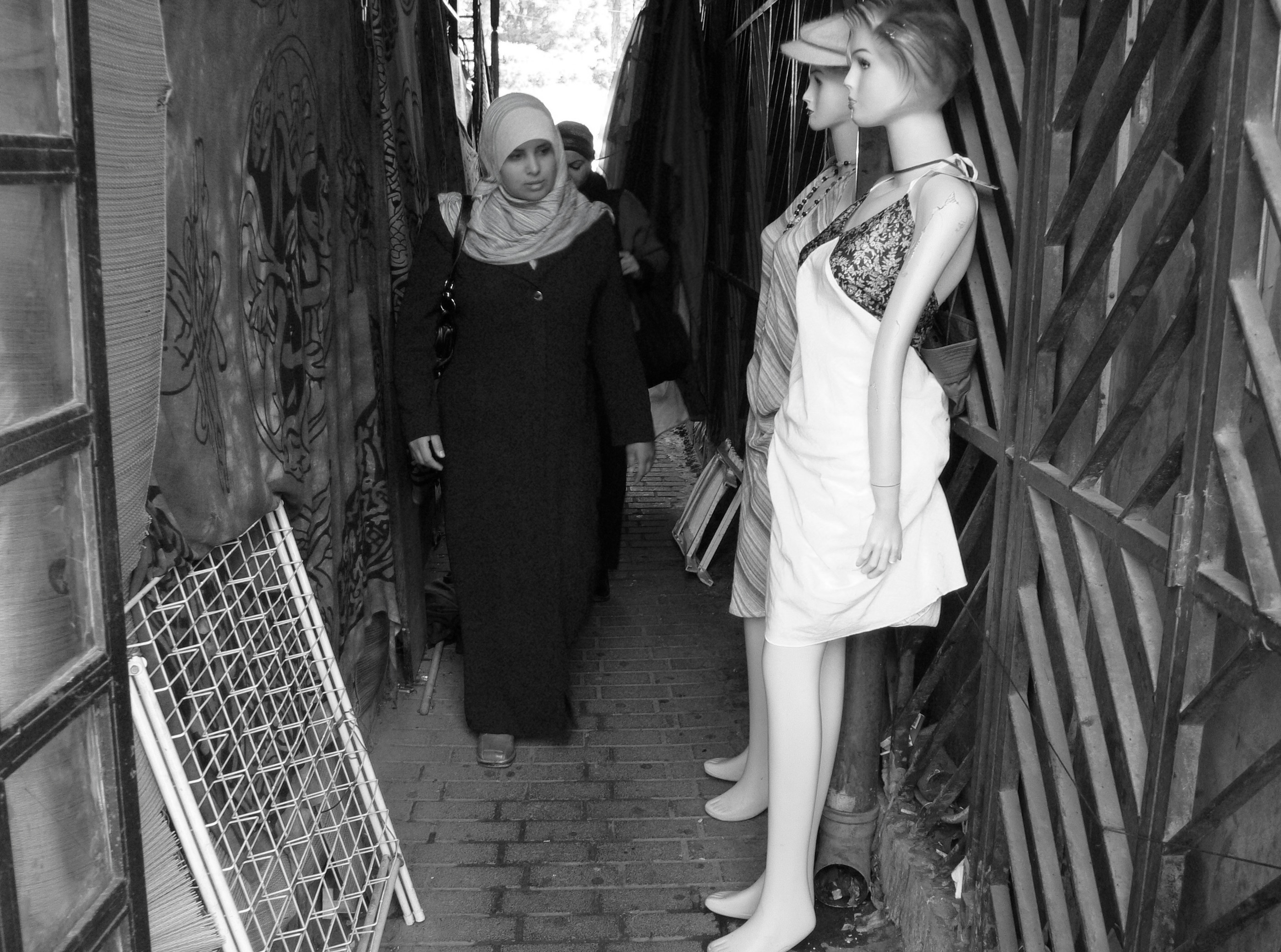 A woman with a head scarf and long black dress walks infront of two female manequins