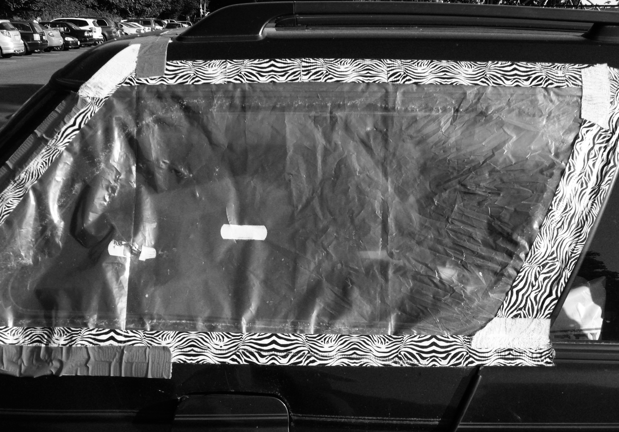 Patterned duct tape and clear plastic cover a broken car window