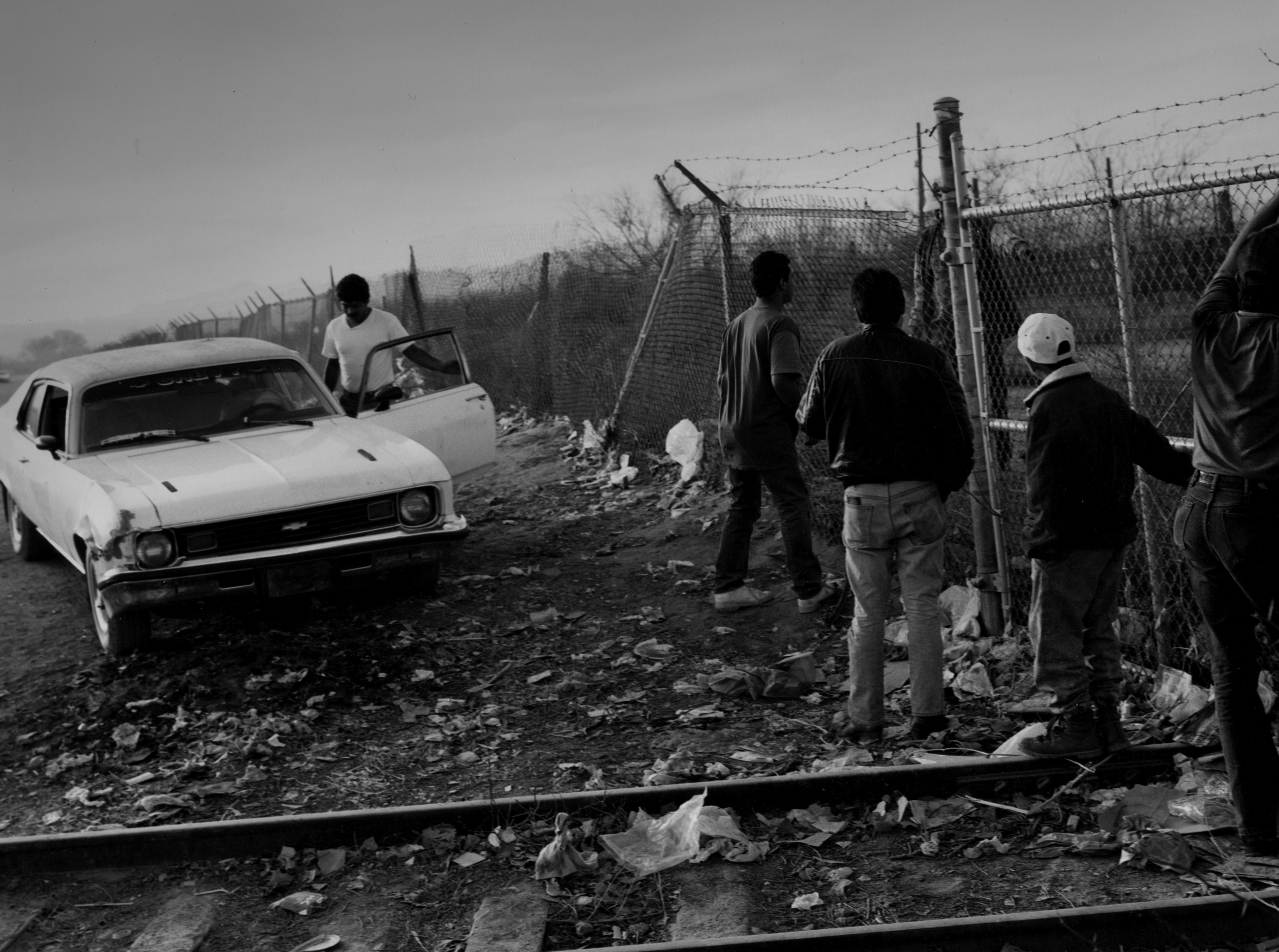 Men wait at a chain link fence while a man gets inside a car