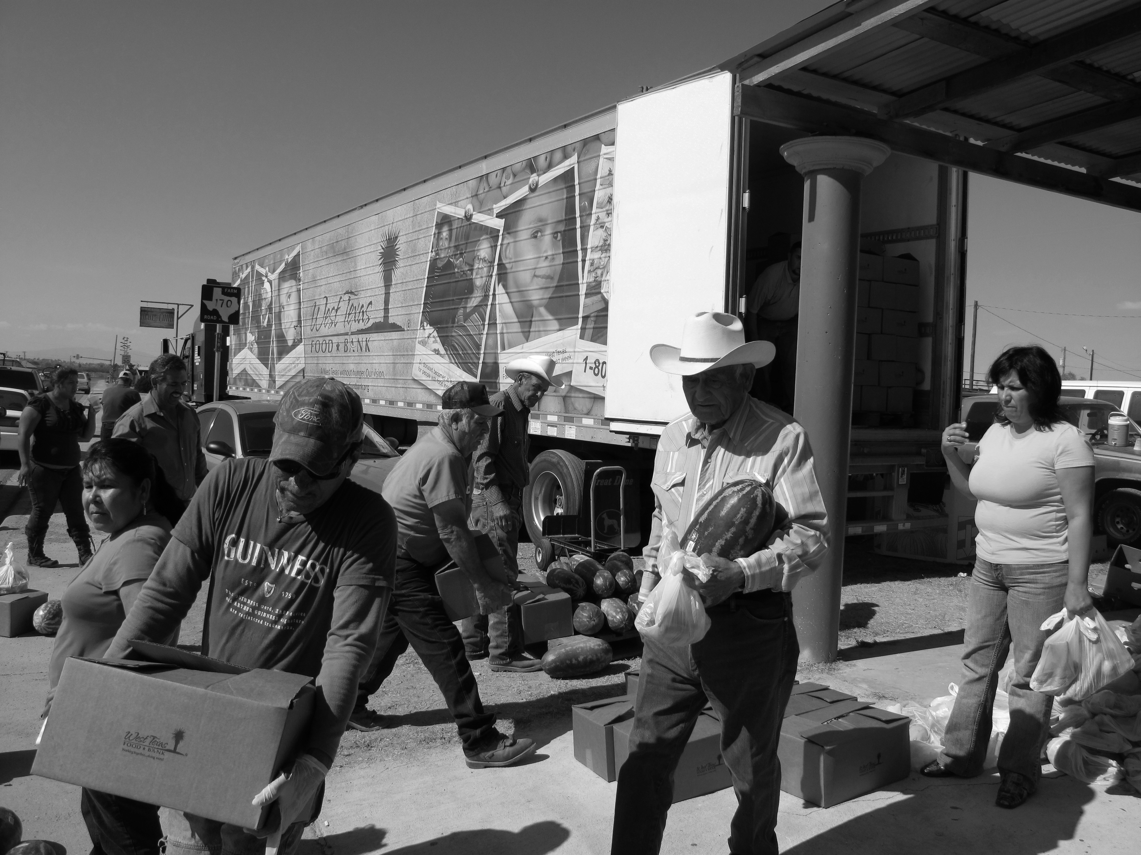 Men and women carry boxes and bags away from a tractor trailer truck