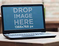 Wide image with laptop on rustic dinner table