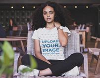 Black Woman Wearing a Tshirt Mockup Sitting on a Wooden