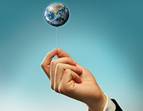 Hand of a Businessman Holding a String of Earth Balloon