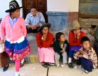 A poor Peruvian family huddles together awaiting a bus.