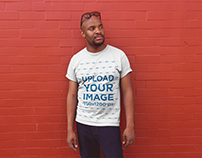 Tshirt Mockup of a Bald Man Posing Against a Red Wall