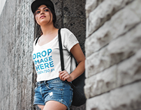 T-Shirt Mockup of a Girl Leaning Against a Stone Wall