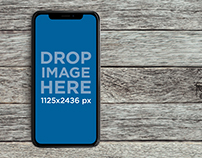 iPhone X Mockup Lying Over a Gray Wooden Surface