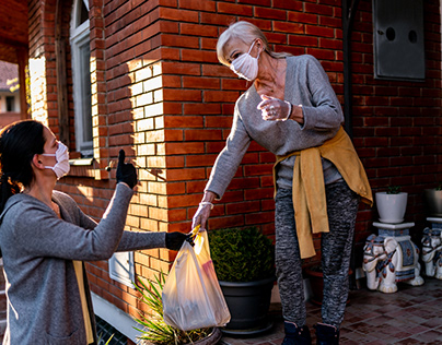 Female volunteer bringing groceries to a woman