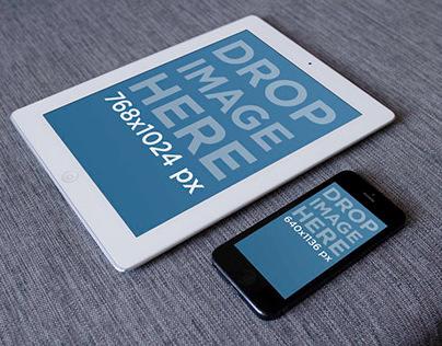 White iPad next to black iPhone on gray fabric
