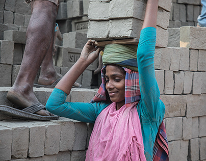 Women carry dried bricks on their heads