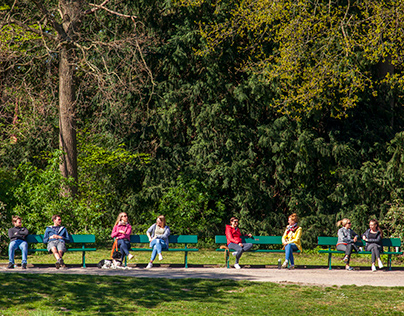 People in pairs on benches in a park in the Corona peri