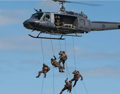 Soldiers dropping down from helicopters.