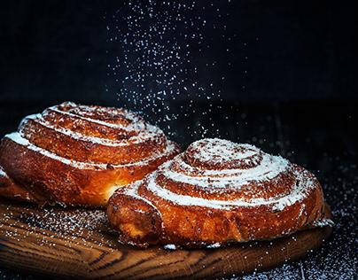 Homemade cinnamon buns with powdered sugar.