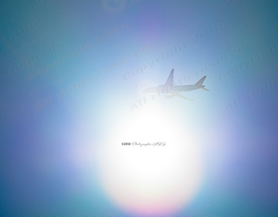 The sun and rainbow color and flare, and the plane