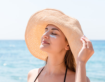 woman is applying sunblock. Sun protection concept.