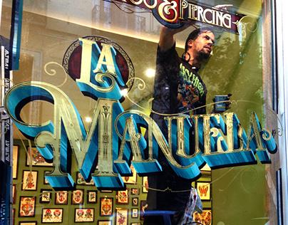 La Manuela Tattoo: Logo and gilded windows