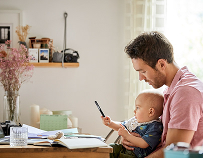 Father Looking at Baby Boy Playing with Pen.