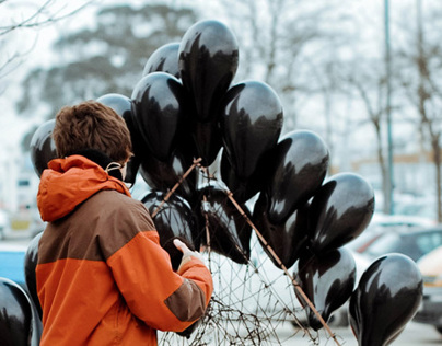 Boy with black balloons